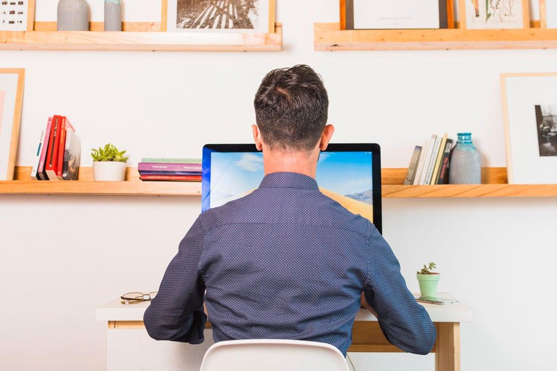 mladi covek sedi ispred svog racunara i radi