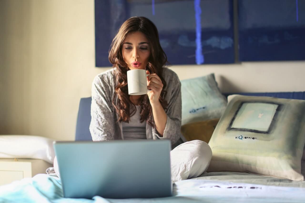 Zena u sivoj jakni sedi na krevetu, pije kafu i radi na laptopu